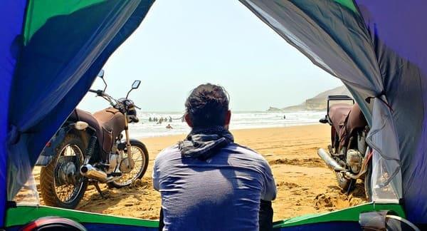 テントからバイクのある景色を眺める人の画像