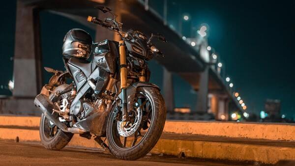 夜景と一緒に写っているバイクとヘルメットの画像