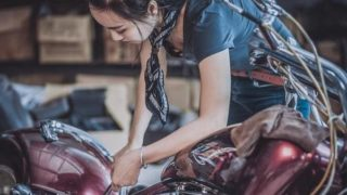 女性がバイクを整備している画像