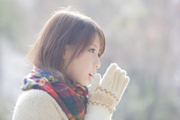 寒くて手を暖めている女性の画像