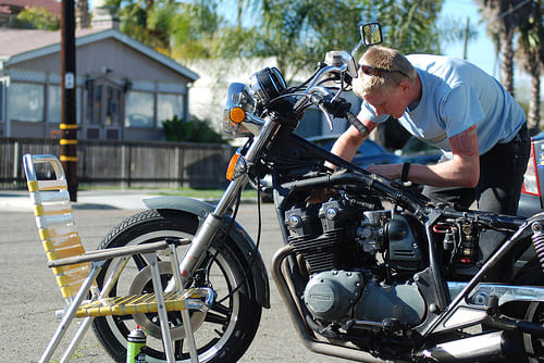 バイクの整備に夢中になる男性の画像